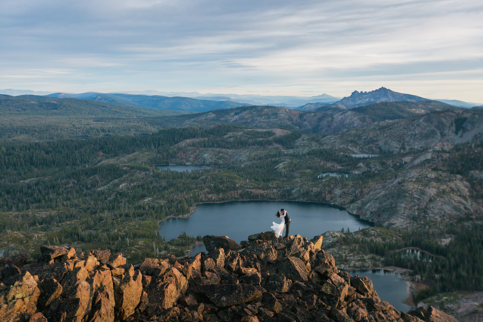 Epic shot of bride and groom embracing on a mountain top.